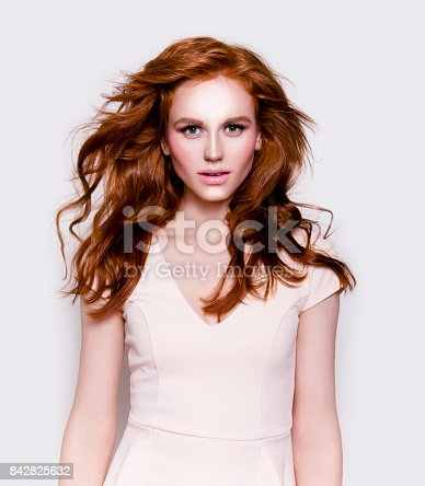 Young beautiful redhead woman with professional make-up looks perfect wearing white dress Fashion model studio portrait on white background