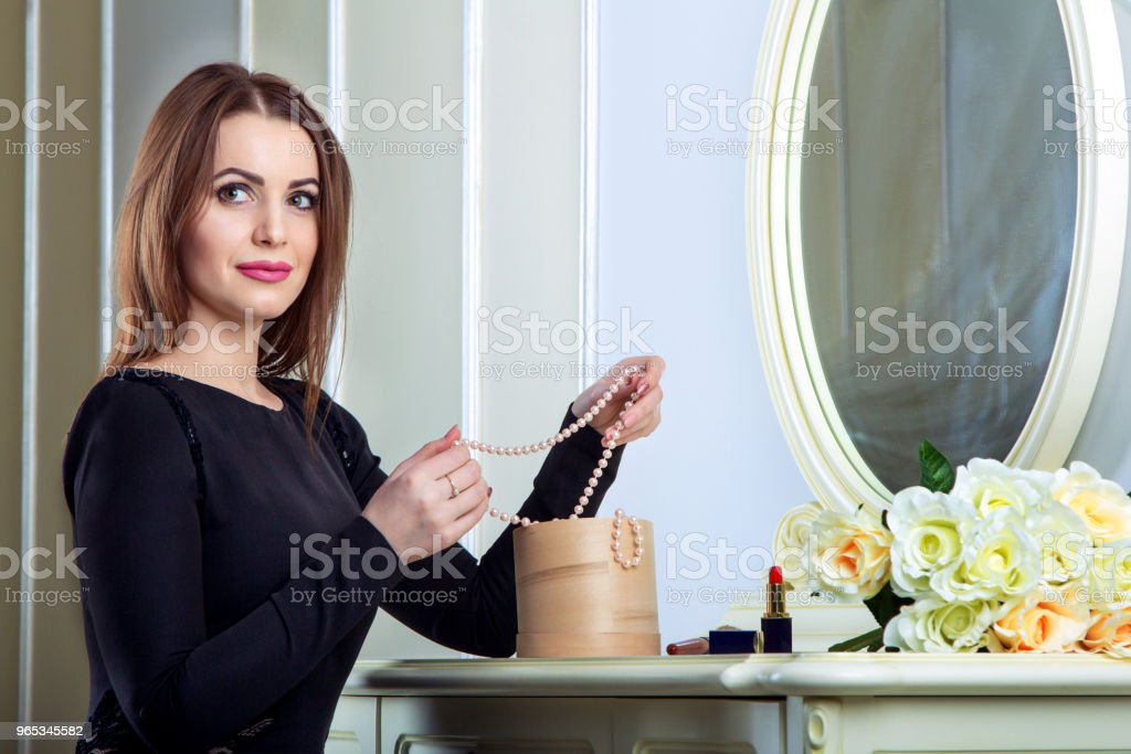 Portrait of beautiful young smiling brunette woman sitting near mirror royalty-free stock photo