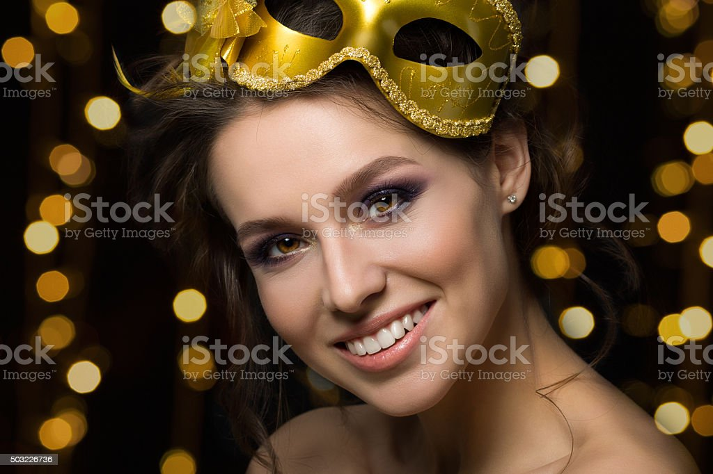 Portrait of beautiful young smiling woman wearing golden party m stock photo