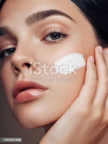 istock Portrait of beautiful young woman applying skin cream 1055652886