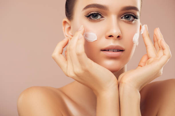 Portrait of beautiful young woman applying skin cream stock photo