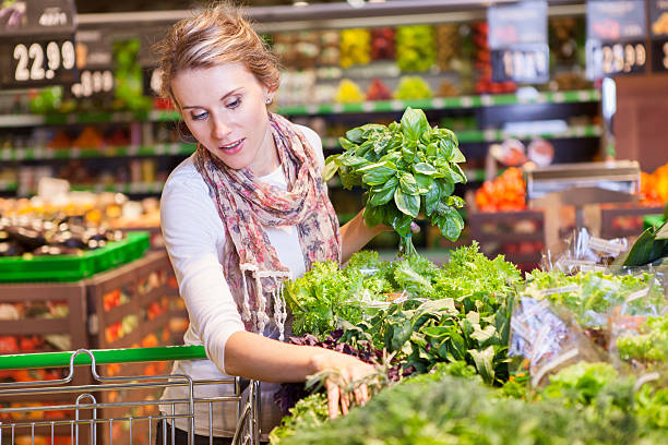 Portrait of beautiful young woman choosing green leafy vegetable – Foto