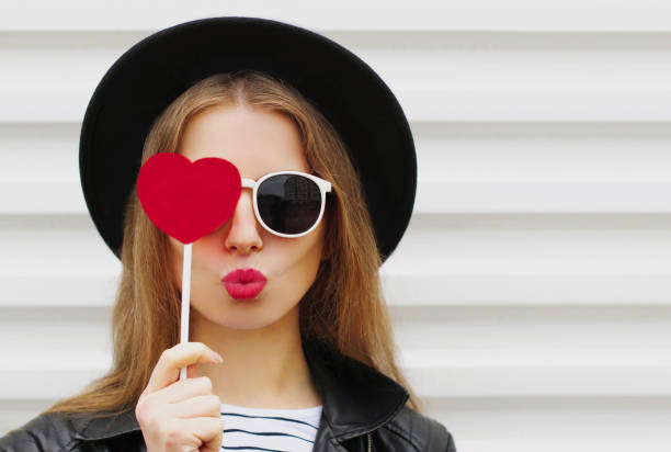 Portrait of beautiful young woman covering her eyes with red heart shaped lollipop blowing red lips sending sweet air kiss on a white background stock photo