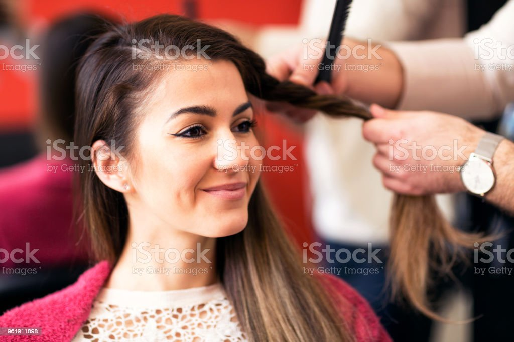 Portrait of beautiful young woman getting haircut royalty-free stock photo