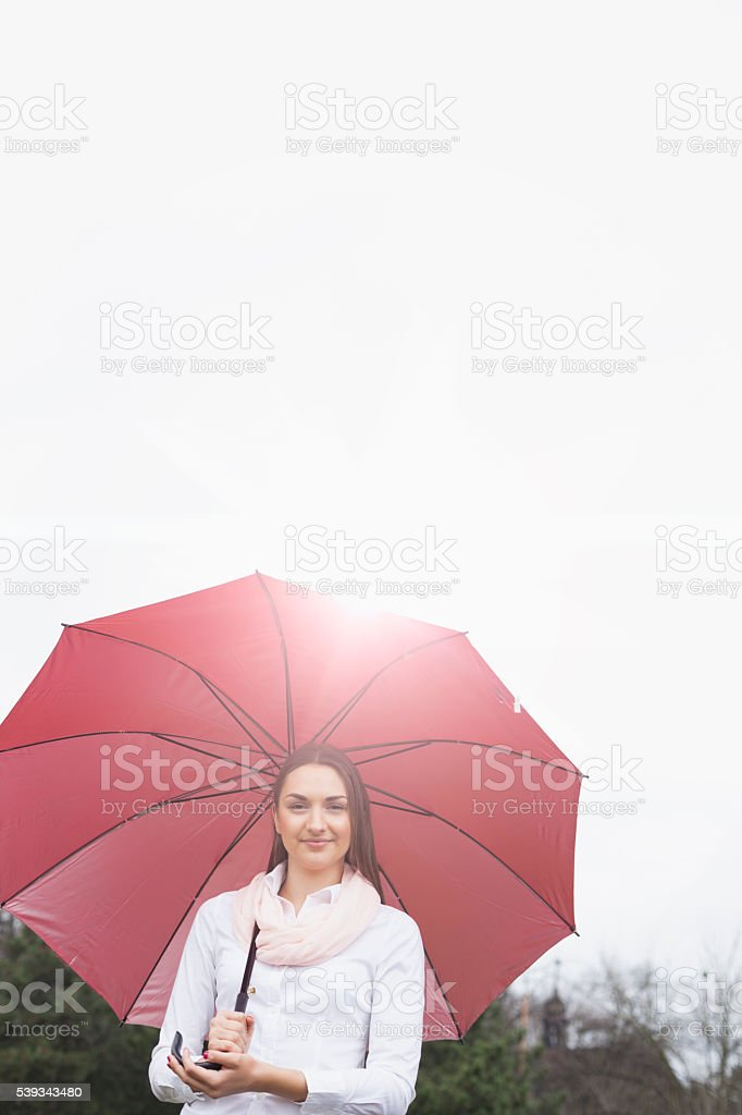Portrait of beautiful young woman holding umbrella against clear sky stock photo