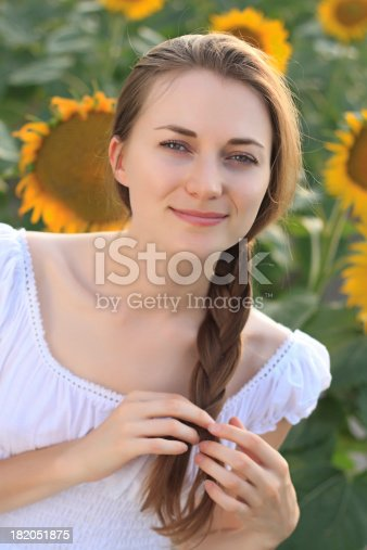 Portrait of beautiful young woman in sunflower field