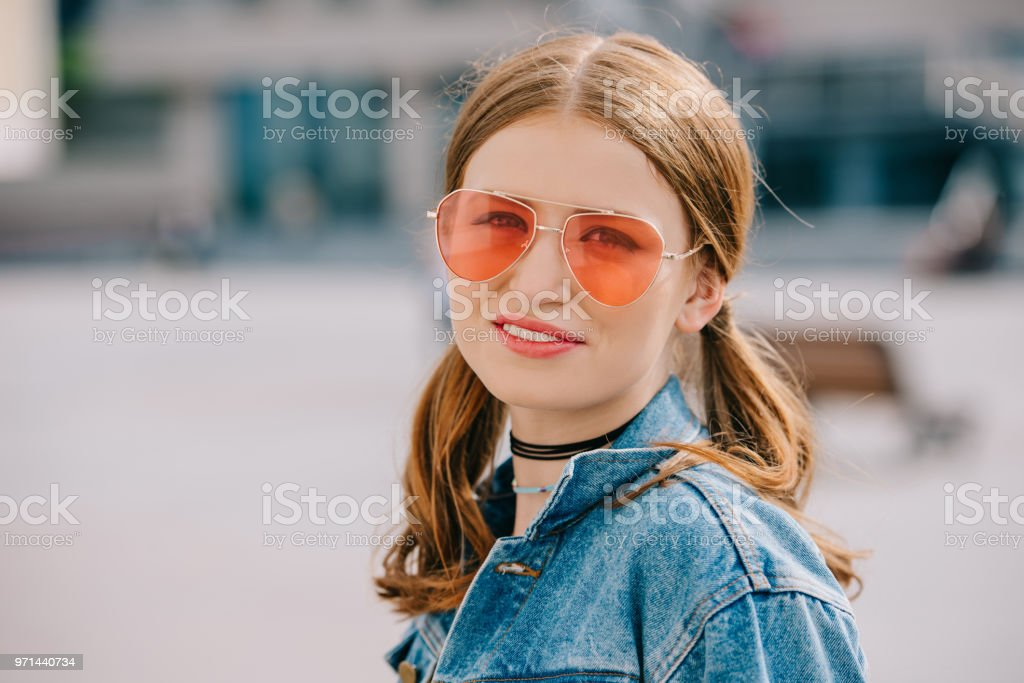 625c980f65 Portrait of beautiful young woman in sunglasses and denim jacket smiling at  camera - Stock image .
