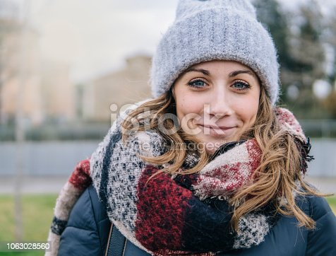 Close-up of young beautiful woman smiling outdoors in winter