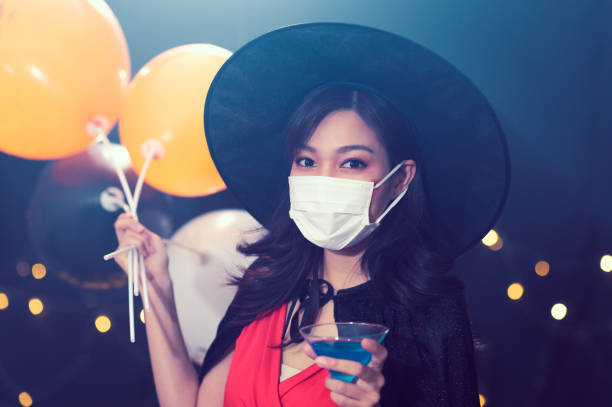 Portrait of beautiful young woman in witch halloween costumes wearing protection face mask against coronavirus drinking cocktails at party over dark magic background - Halloween party concept Portrait of beautiful young woman in witch halloween costumes wearing protection face mask against coronavirus drinking cocktails at party over dark magic background - Halloween party concept halloween covid stock pictures, royalty-free photos & images