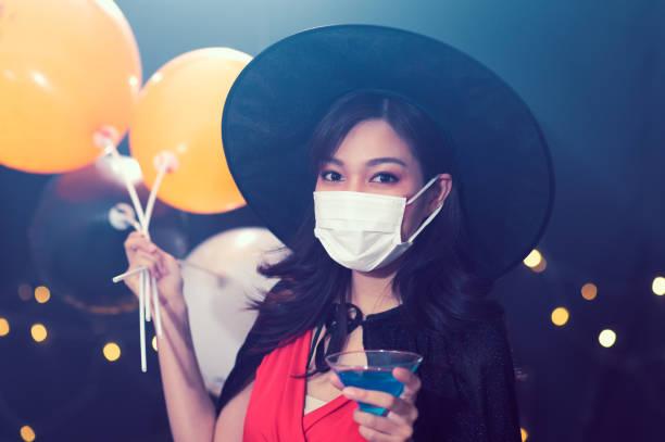 retrato de hermosa joven en trajes de bruja halloween que llevan máscara facial de protección contra cócteles de coronavirus en la fiesta sobre el fondo mágico oscuro - concepto de fiesta de halloween - halloween covid fotografías e imágenes de stock