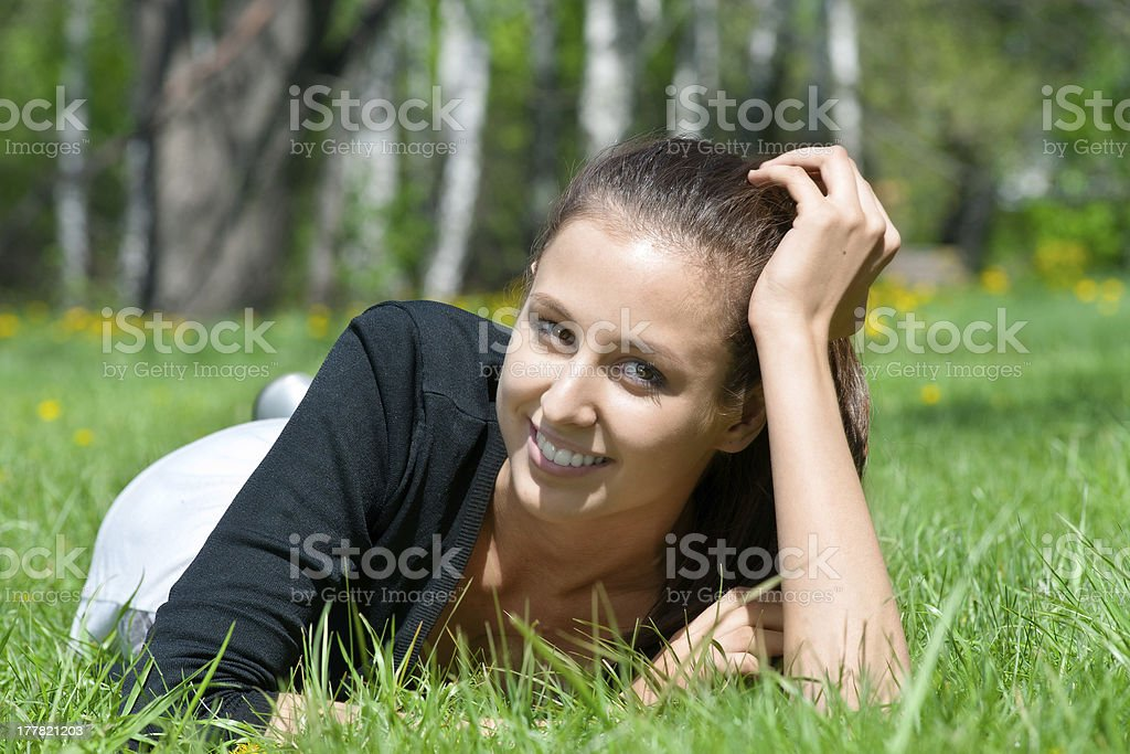 Portrait of beautiful young woman lying on grass royalty-free stock photo