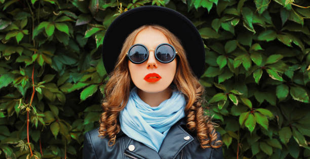 Portrait of beautiful young woman model wearing a black round hat, jacket, sunglasses over green leaves wall as background stock photo