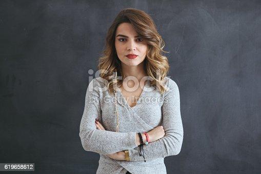 istock Portrait of beautiful young woman on blackboard 619658612