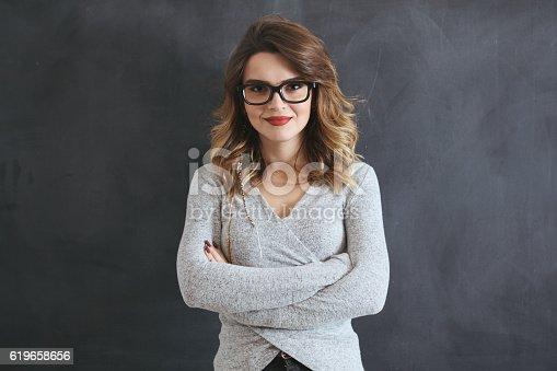 istock Portrait of beautiful young woman on blackboard 619658656