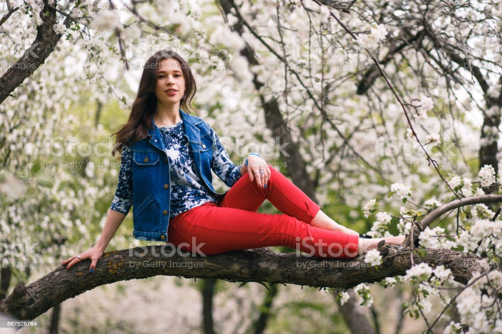 Portrait of beautiful young woman sitting on the tree branch in blossoming garden. foto stock royalty-free