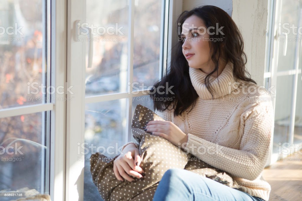 Portrait of Beautiful Young Woman Smiling in a knitted sweater about a window. Christmas morning. Fall stock photo