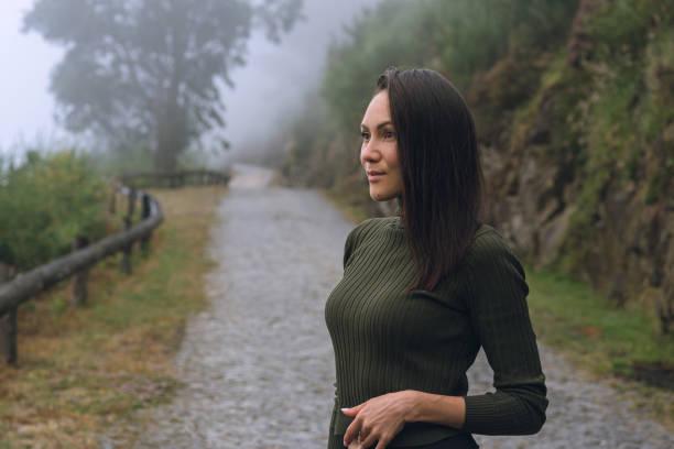 retrato de una hermosa joven de pie en el fondo de un camino de montaña - lifestyle color background fotografías e imágenes de stock