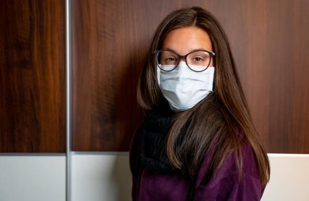 Porträt der schönen jungen Frau trägt chirurgische Maske und Brille während der Pandemie - Stockfoto – Foto