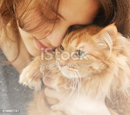 istock portrait of beautiful young woman with a cat 516982741