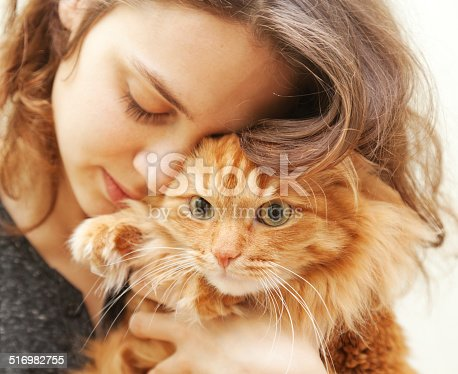 istock portrait of beautiful young woman with a cat 516982755
