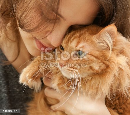 istock portrait of beautiful young woman with a cat 516982771