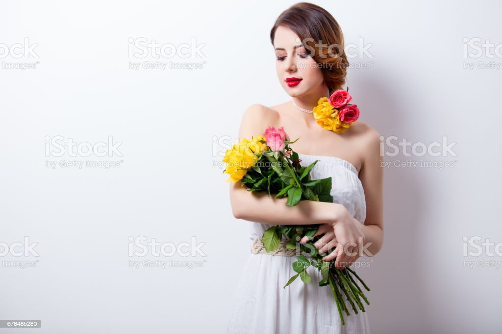 portrait of beautiful young woman with bouquet of roses on the wonderful studio background royalty-free stock photo