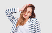 istock Portrait of beautiful young woman with long hair has joyful expression. Charming female smiling with closed eyes, enjoying the day and showing her healthy hair. 1167963946