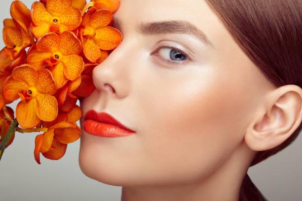 porträt der schönen jungen frau mit orchidee - blumen make up stock-fotos und bilder