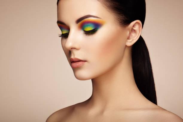 porträt der schönen jungen frau mit regenbogen make-up - regenbogen make up stock-fotos und bilder
