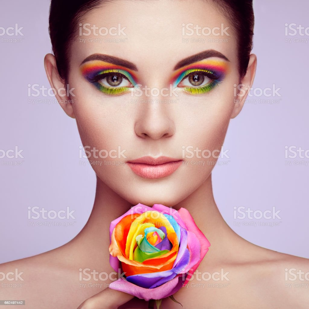 Portrait of beautiful young woman with rainbow rose Стоковые фото Стоковая фотография