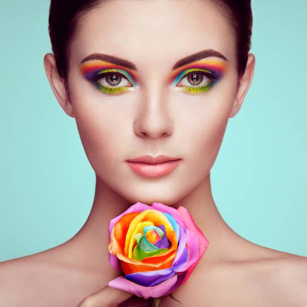 porträt der schönen jungen frau mit regenbogen rose - regenbogen make up stock-fotos und bilder