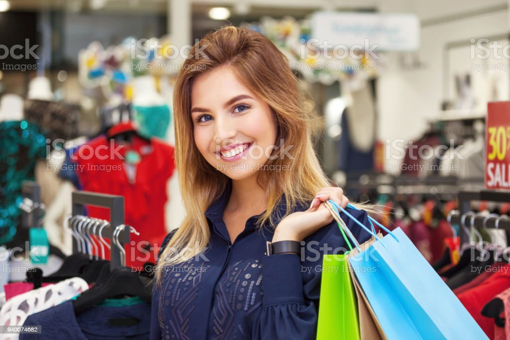4e71257324 Portrait of beautiful young woman with shopping bags in clothing store. -  Stock image .