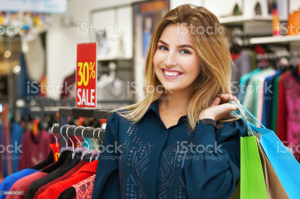 b7b20d64c3 Portrait of beautiful young woman with shopping bags in clothing store.  royalty-free stock