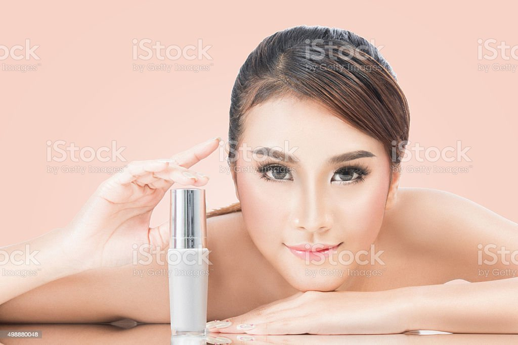 Portrait of Beautiful Young Woman with skincare product. stock photo