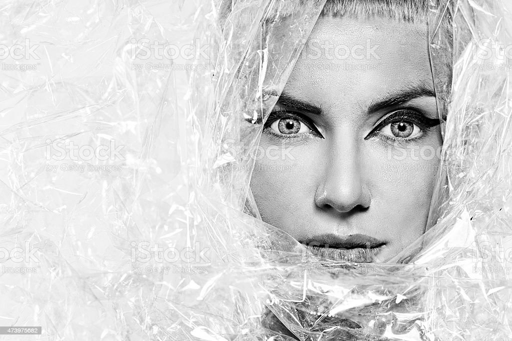 Portrait of beautiful young woman, wrapped in cellophane stock photo