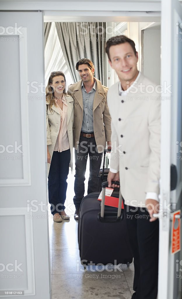 Portrait of bellman opening hotel room door with couple in background stock photo