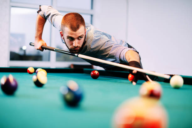 portrait of billiard player aiming during tournament - pool cue stock photos and pictures