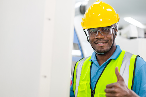 Portrait of black African American male worker in protection glasses and helmet smile showing thumbs up in front of industry machine at industrial factory. quality control guarantee with copy space