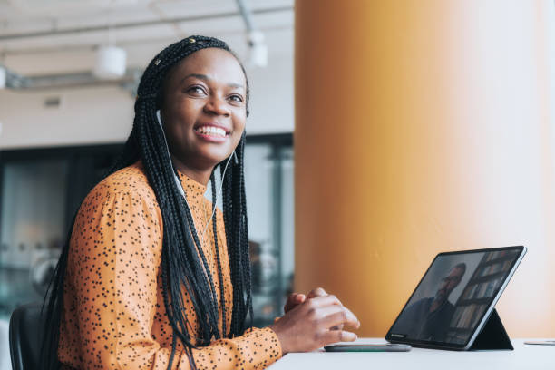 portrait of black business woman with tablet in video call stock photo
