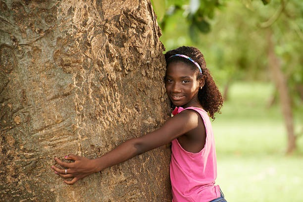 Portrait of black ecologist girl hugging tree and smiling Ecology and environment-Portrait of young african american girl embracing and hugging tree in park, smiling and looking at camera tree hugging stock pictures, royalty-free photos & images