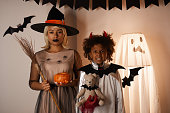 istock Portrait of black family in Halloween costumes standing against wall decorated with ghost mannequin and paper rats 1171720760