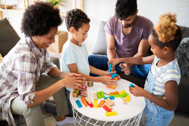 Porträt der schwarzen Familie, die ein Spiel zu Hause zusammen spielt – Foto