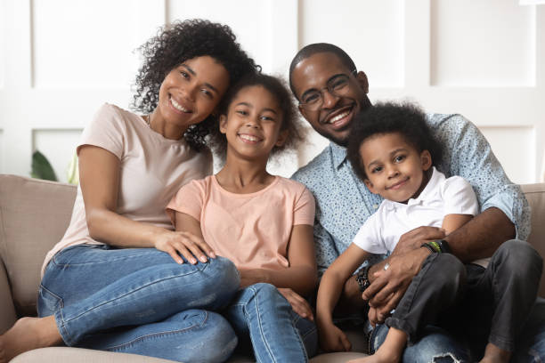Portrait of black family with kids relax on couch Portrait of happy young african American family with little kids sit relax on couch cuddling, smiling black parents rest on sofa hug preschooler children posing for picture at home together black ethnicity stock pictures, royalty-free photos & images