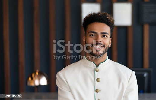 Portrait of black friendly bellhop working at hotel looking at camera very happy and smiling