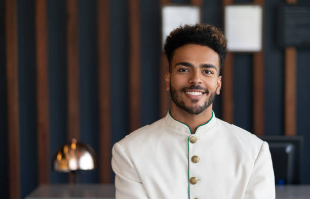 Portrait of black friendly bellhop working at hotel looking at camera very happy stock photo