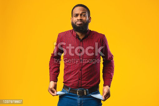 istock Portrait of black guy showing empty pockets 1237979907