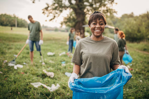 Portrait of black woman with group of volunteers cleaning nature together stock photo