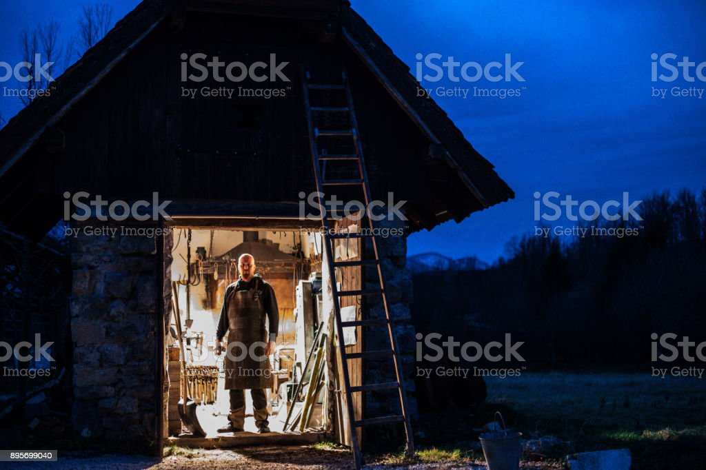 Portrait of Blacksmith and his Forge at Twilight stock photo