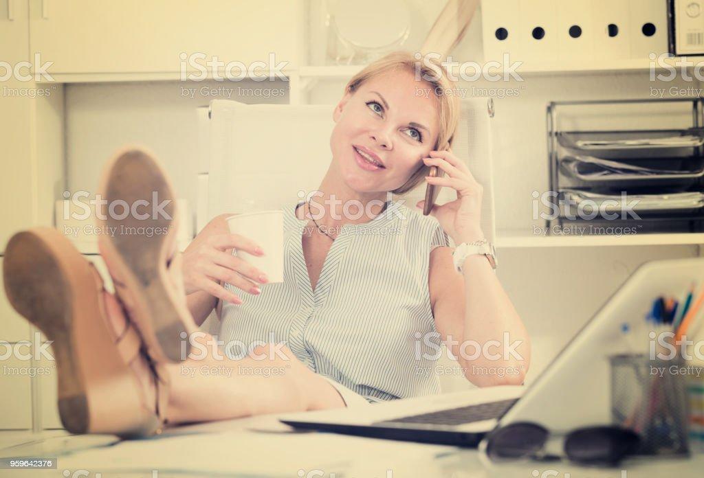 Retrato de mujer rubia en la oficina hablando por móvil - Foto de stock de 20 a 29 años libre de derechos