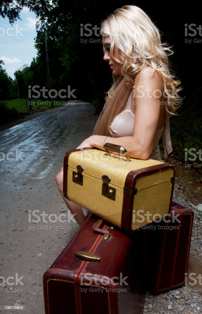 Portrait of Blond Woman Sitting on Luggage Near Dirt Road royalty-free stock photo